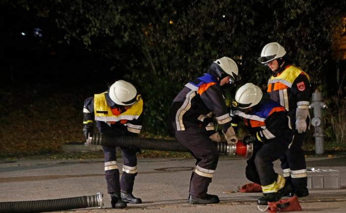 Vier Feuerwehrleute kuppeln eine Saugleitung.